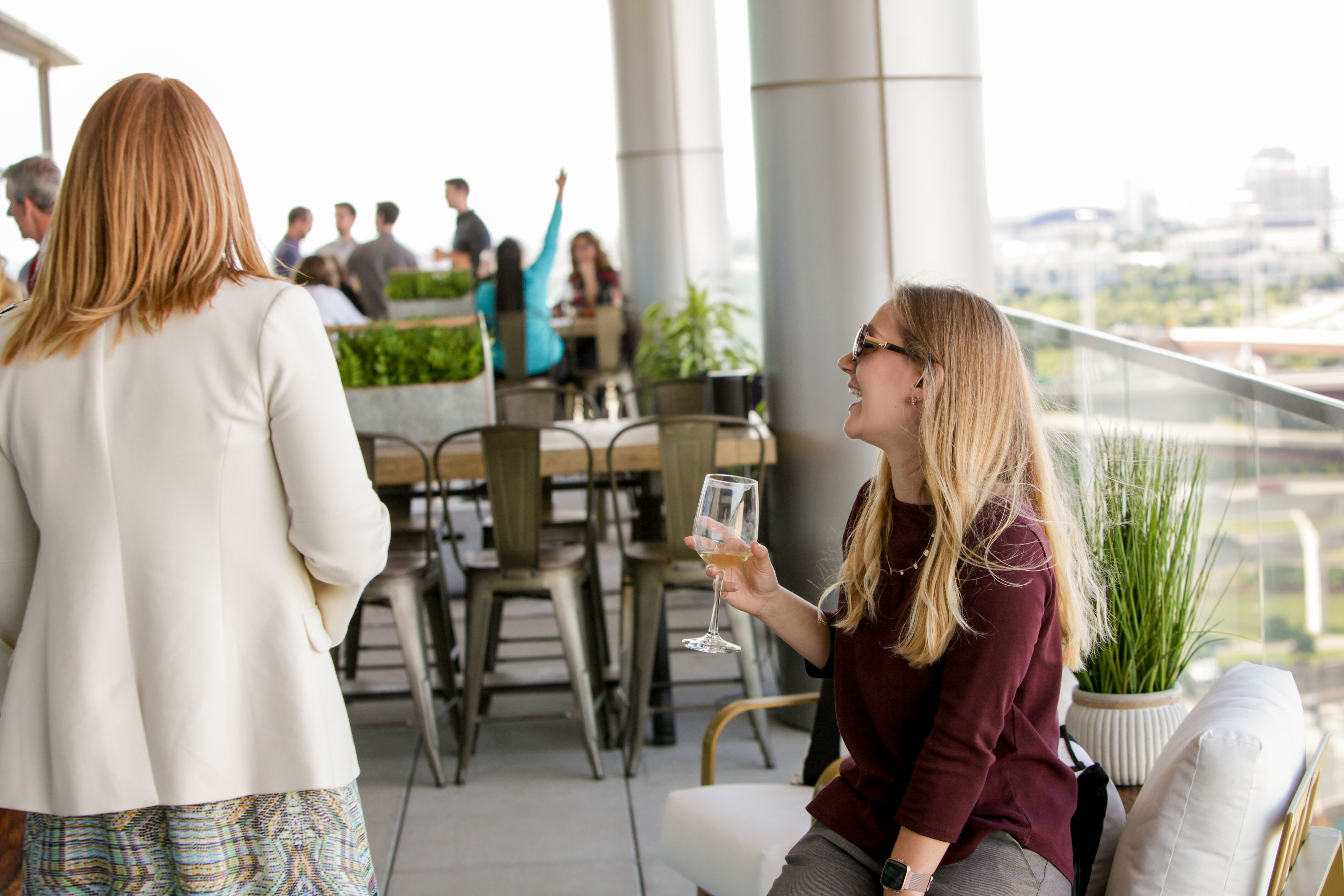 Colleagues and clients enjoy drinks on the Lifeblue balcony during the official grand opening for the new office.