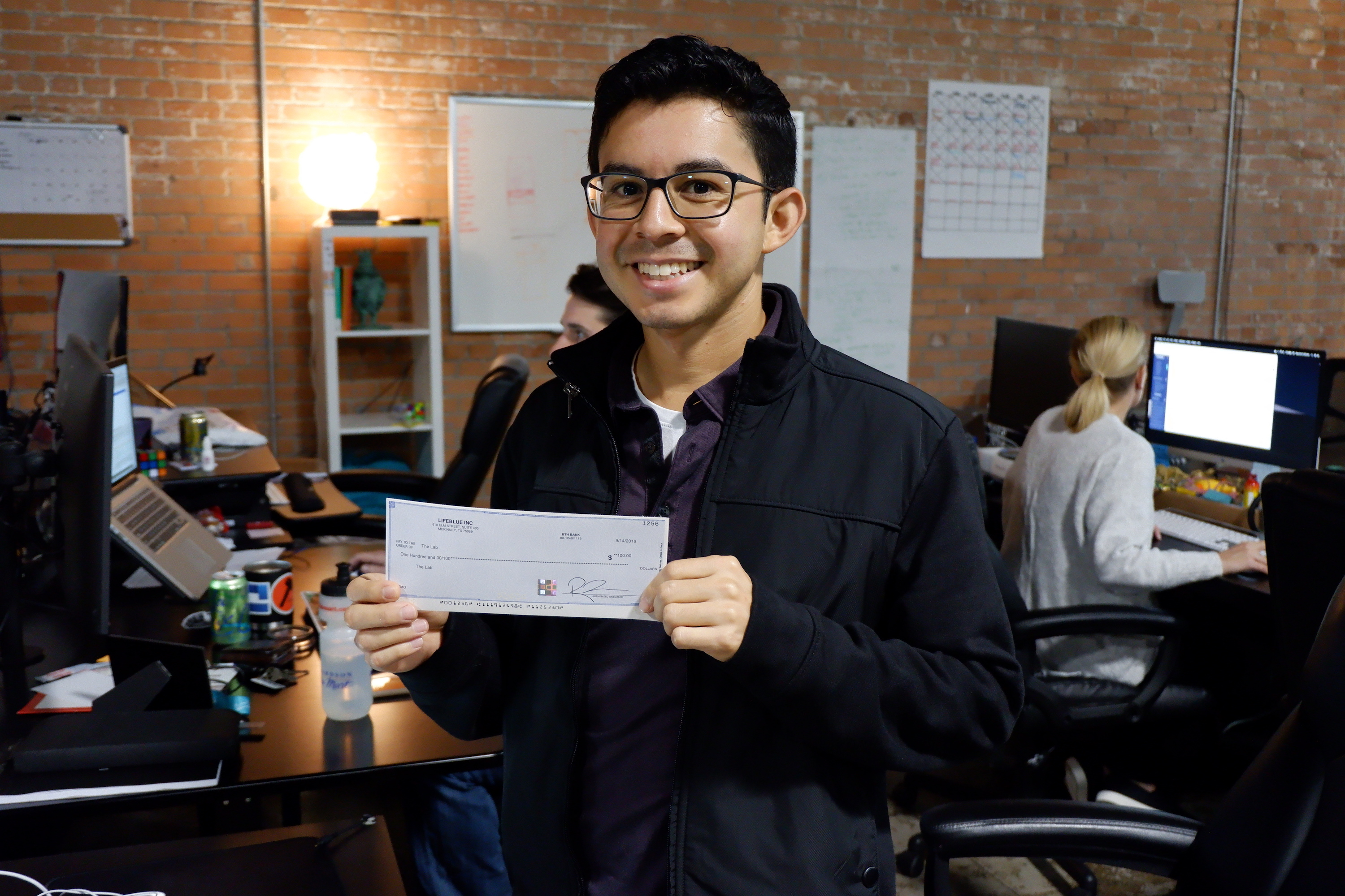 Back End Developer Anthony holding the prize check for his charity.