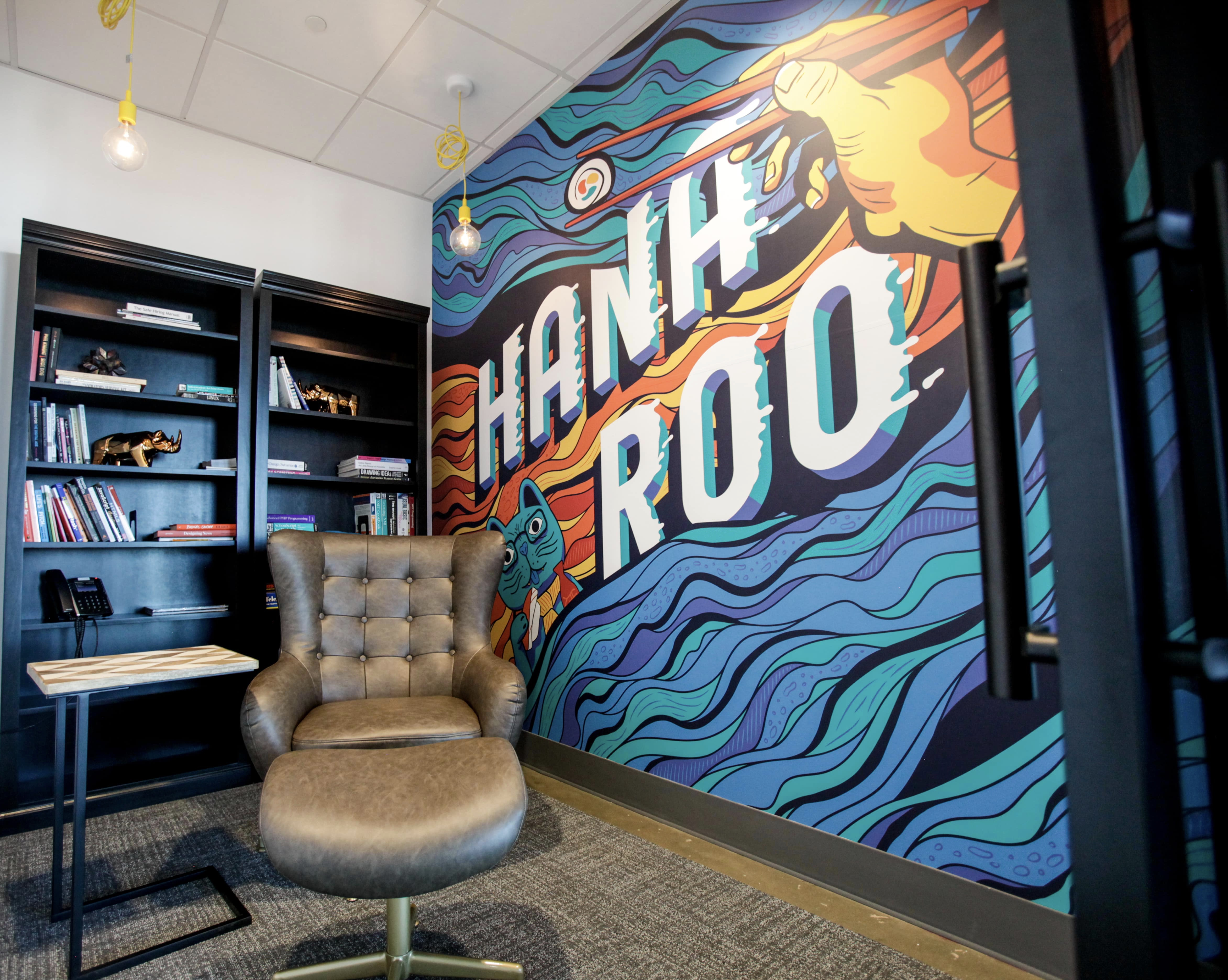 The smallest meeting room is a named Hanaroo, paying homage to a memorable sushi joint in Little Rock where the bravest would venture during trips to Heifer International. It features one of several murals around the office, this one depicting chopsticks, and an adorable cat amidst waves and the word