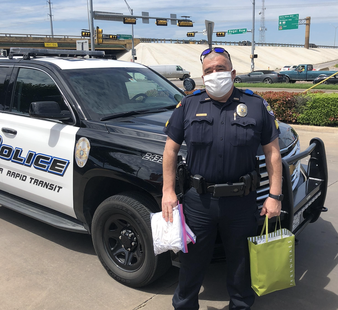 A DART police officer wearing a mask and holding bags of other masks stands in front of his patrol vehicle on a clear, blue day.