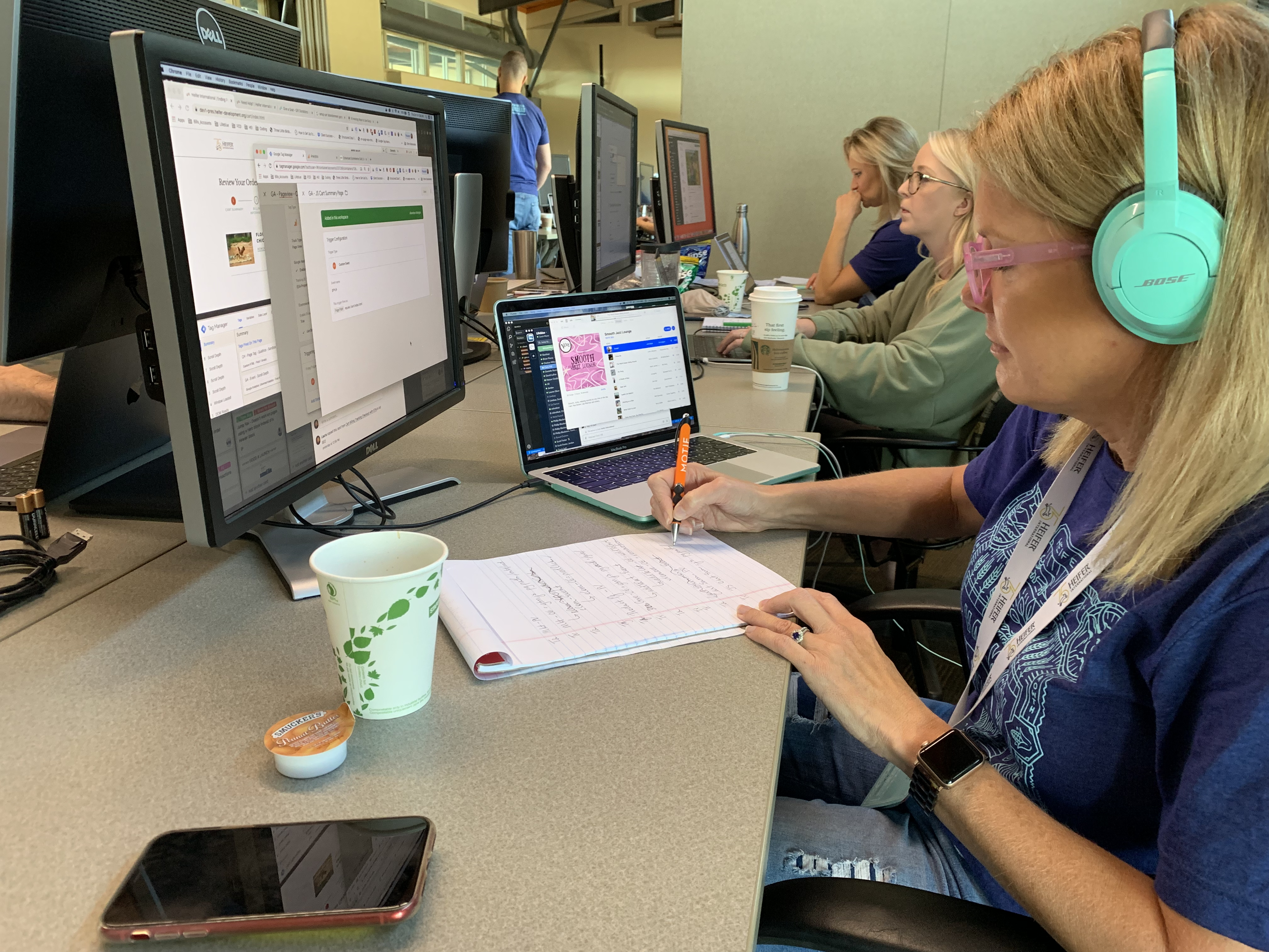 A Lifeblue team member with bright turquoise headphones writes on a pad of paper, while looking at a screen connected to her laptop. In the background are two other people working on computers.