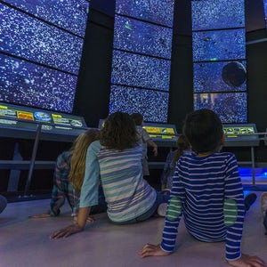 Children in front of stars that are displayed on screens, showing a sense of wonder.