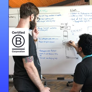 Developer and designer sketching together at a white board next to B Corp logo.